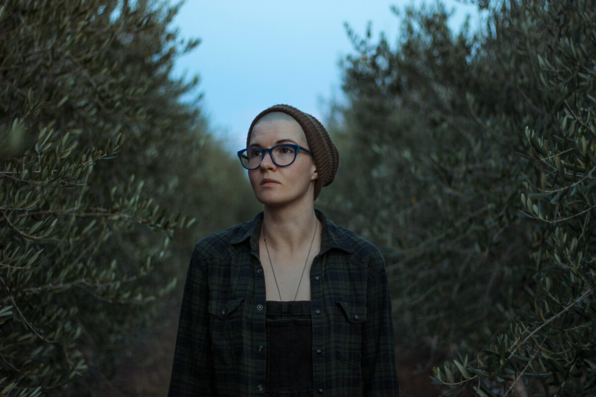 color portrait of Tracy standing between two rows of olive trees