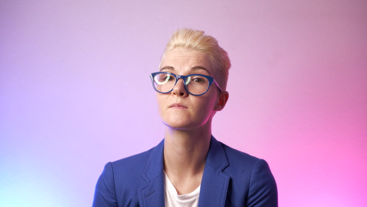 portrait of Tracy in blue glasses and a blue blazer against a blue and pink gradient